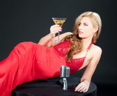 Sexy blond woman in red dress with retro microphone and glass of martini and olive over dark background — Stock Photo