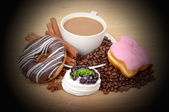 Coffee cup, cinnamon, anise on coffee beans, sweet cakes on the background — Stock Photo