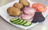 Grilled pork with boled potato, vegetables and bread. with lens effect — Stock Photo
