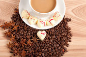 Cup of coffee with beans and white chocolate heart candy over wooden background — Stock Photo