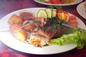 Gegrilde biefstuk, gebakken aardappelen en groenten met mes en vork. — Stockfoto