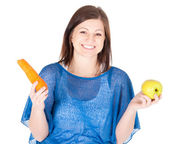 Young woman chose between apple and carrot over white background — Stock Photo