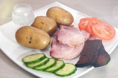 Grilled pork with vodka, boled potato, vegetables and bread. with lens effect — Stock Photo