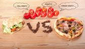 Tasty hamburger and pizza. vesrsus. vs. and some tomatoes — Stock Photo
