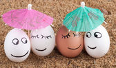 Easter funny eggs under umbrella on a sand — Stock Photo