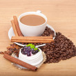 Coffee cup with coffee beans ans sweet cake on a wooden background — Stock Photo #21715515