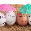 Stockfoto: Easter funny eggs under umbrellon sand