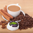 Coffee cup with coffee beans ans sweet cake on a wooden background — Stock Photo #21719185