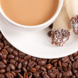 Coffee cup, anise on coffee beans, sweets on the wooden background — Stock Photo