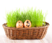 Funny smiling egg with golden dollar egg in basket with grass. — Stock Photo