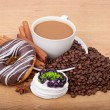 Coffee cup with coffee beans ans sweet cake on a wooden background — Stock Photo #22093587