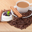 Coffee cup with coffee beans ans sweet cake on a wooden background — Stock Photo