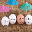 Stock Photo: Easter funny eggs under umbrellon sand