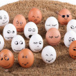 Group of Funny crazy smiling eggs on a sand — Stock Photo