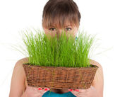 Beautiful woman holding easter basket with green grass — Stock Photo