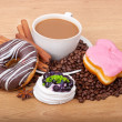 Coffee cup with coffee beans ans sweet cake on a wooden background — Stock Photo #22450417