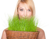 Woman holding easter basket with green grass — Stock Photo