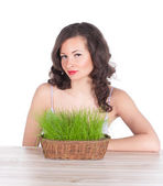 Beautiful woman with easter basket with green grass — Stock Photo
