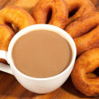 Royalty-Free Stock Photo: Coffee cup and oil donuts on a wooden plate