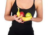 Beautiful fitness young woman with bananas and apples. — Stock Photo