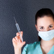 Nurse or doctor with syringe and mask — Stock Photo #25013777