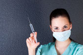 Nurse or doctor with syringe and mask — Stock Photo