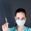 Nurse or doctor with syringe and mask — Stock Photo #25935523