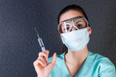 Nurse or doctor in pilot glasses with syringe and mask — Stock Photo