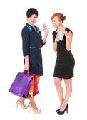 Dva usmívající se womenwith nákupní tašky drží peníze — Stock fotografie