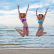 Happy excited young women in bikini jumping on beach — Stock Photo #27358991