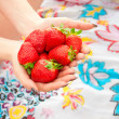 图库照片: Girl Holding Handful Of Strawberries