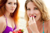 Two beautiful young women eating a strawberry. — Stock Photo