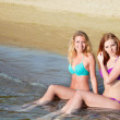 Two beautiful young women sitting in water on a beach. — Stock Photo #27360577