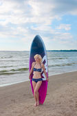 Pretty blond girl model like Marilyn Monroe with surfing board on a beach — Stock Photo