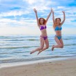Happy excited young women in bikini jumping on beach — Stock Photo #28688197