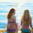 Two beautiful young women sitting in water on a beach. — Stock Photo