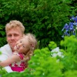 Happy father and little girl at a garden — Stock Photo