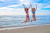 Happy excited young women in bikini jumping on beach — Stock Photo