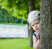 Kleine jongen zich te verbergen achter de boom — Stockfoto