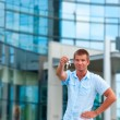 Stock Photo: Business man holding a key in front of modern business building