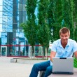 Business manwith laptop in front of modern business building — Stock Photo
