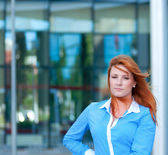 Business woman with red hair in front of office building. — Stock Photo