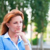 Thinking business woman with red hair — Stock Photo