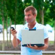 Business man with laptopand mobile phone in front of modern business building — Stock Photo