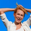 Beautiful woman smiling portait in white shirt over blue sky  — Stock Photo