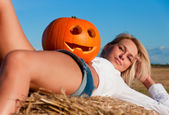 Beautiful woman posing on a bale with pumpkin — Stock Photo