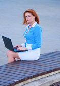 Business woman posing with a laptop in a front of office building — Stock Photo