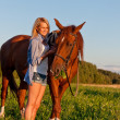 Stock Photo: Young girl walking with horse in field