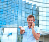 Business man speaking on phone in front of modern business building — Stock Photo
