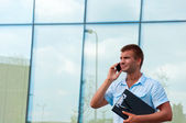 Business man with notebook and mobile phone in front of modern business building — Stock Photo